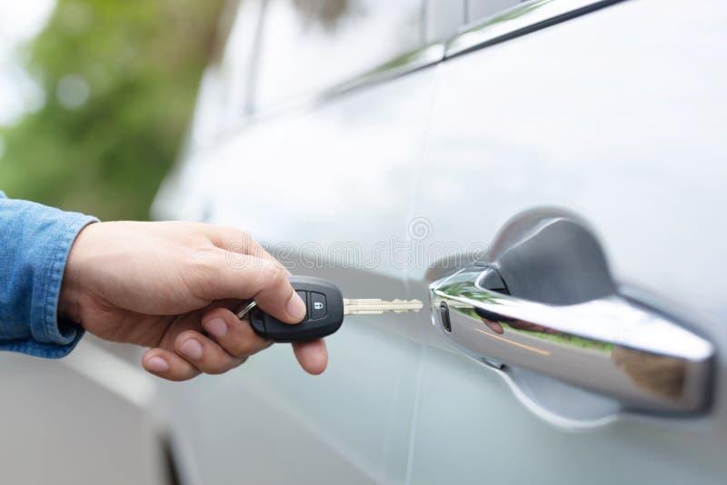 汽车钥匙在商人手上 在遥控汽车报警系统的手新闻 免版税库存图片