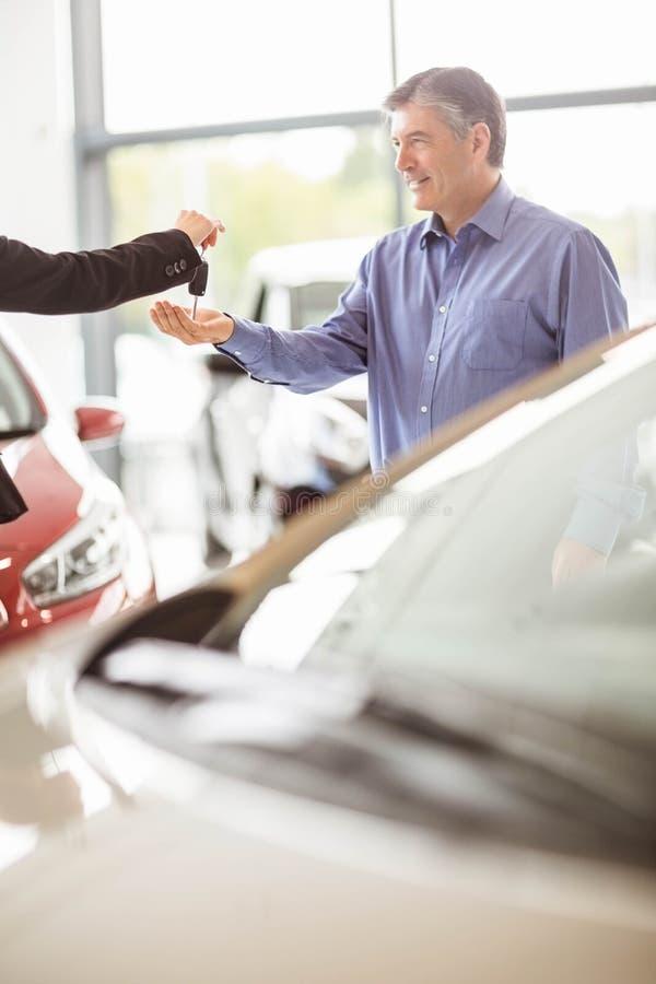 给汽车钥匙的女推销员,当握客户的手时 图库摄影