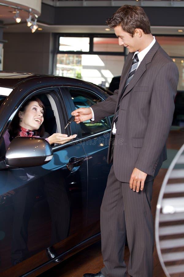 给汽车钥匙的汽车推销员一个少妇 免版税库存照片