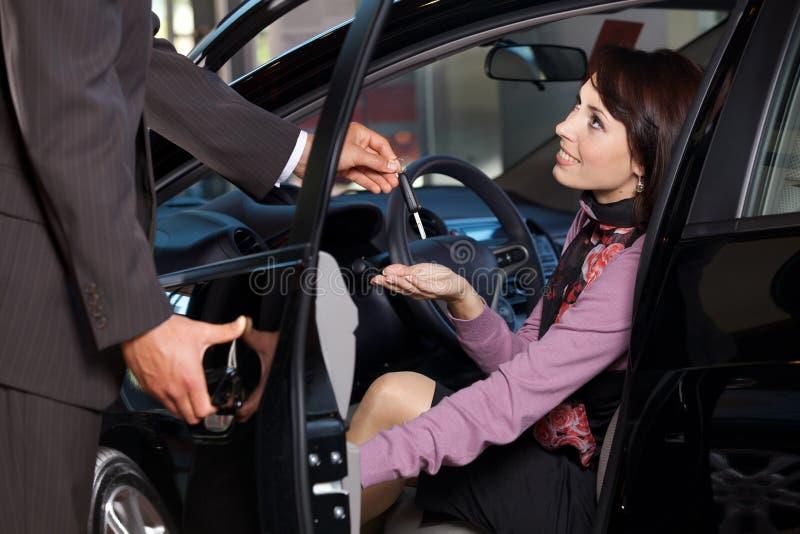 给汽车钥匙的汽车推销员一个少妇 库存图片