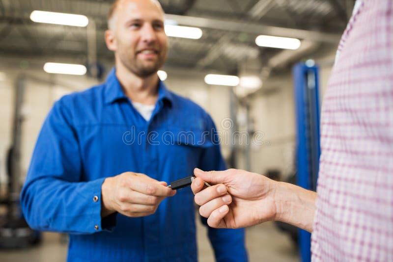 给汽车钥匙的汽车机械师人在车间 免版税库存图片