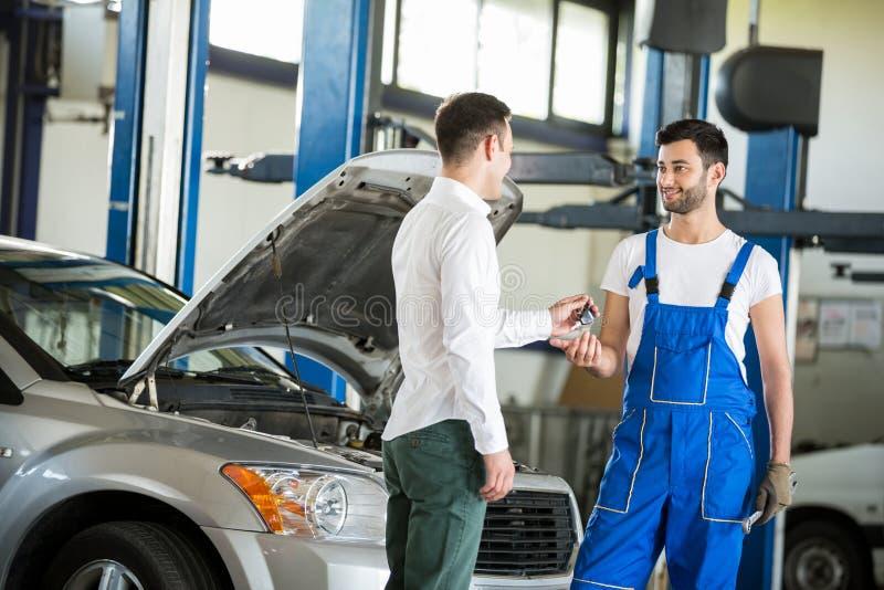 给他汽车钥匙的顾客技工 免版税库存图片