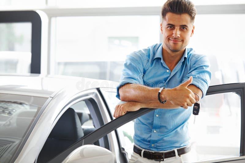 汽车陈列室 有钥匙的愉快的人的他的梦想汽车  免版税库存图片