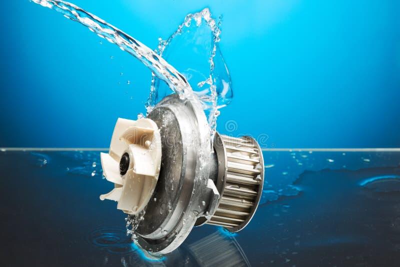 汽车零件,在水飞溅的引擎冷却的泵浦在蓝色backgrou 免版税库存照片
