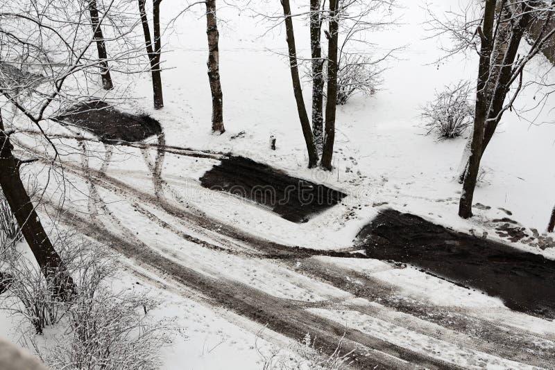 汽车黑暗的踪影在雪路的 图库摄影