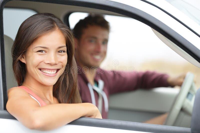 汽车-驾驶在新汽车微笑的夫妇愉快 免版税图库摄影