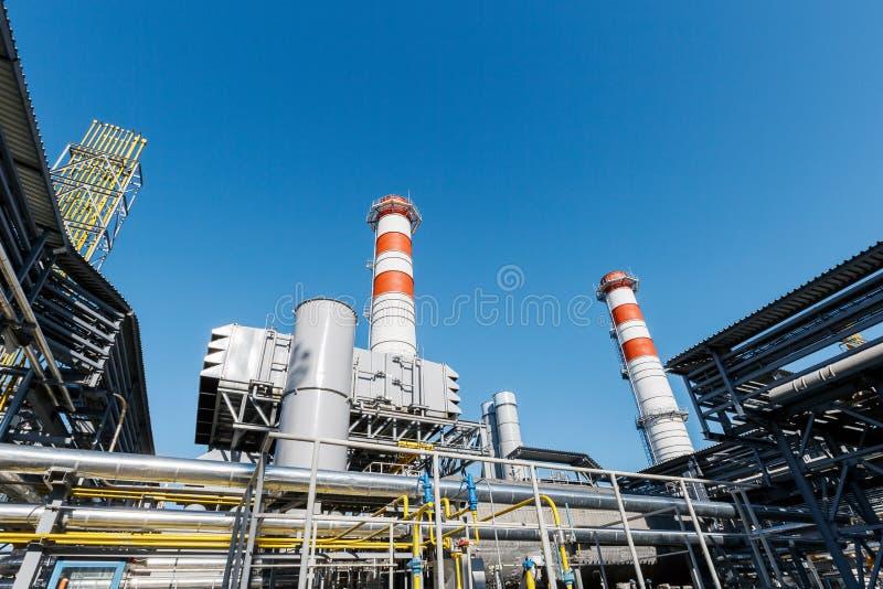 汽轮机天然气的能源厂与红白的颜色烟囱反对一天空蔚蓝的在一好日子 库存照片
