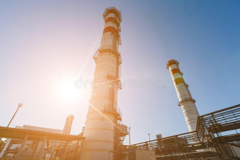 汽轮机天然气的能源厂与红白的颜色烟囱反对一天空蔚蓝的在一好日子 免版税库存照片