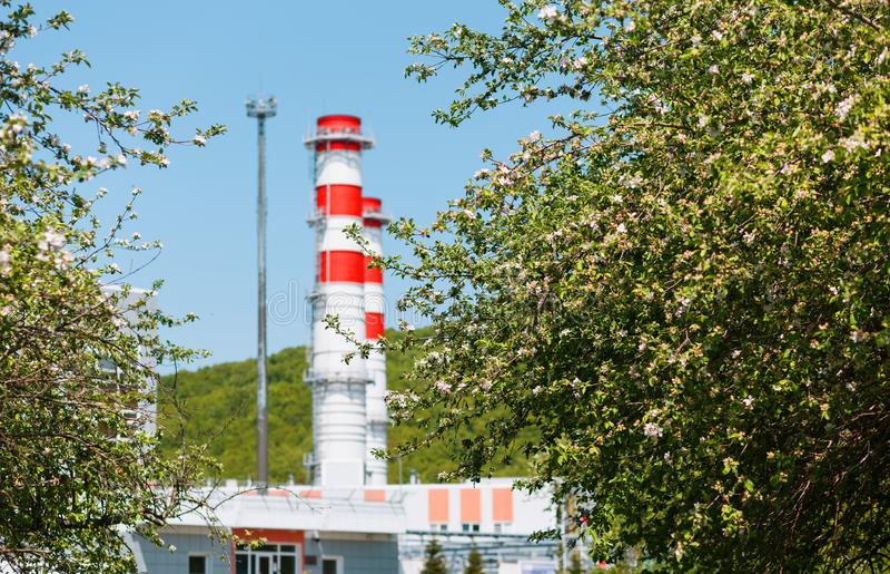 汽轮机天然气的能源厂与红白的颜色烟囱反对天空蔚蓝的在苹果树 免版税图库摄影