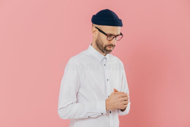 沉思不剃须的人保留注视,戴白色衬衫、帽子和眼镜,深深在想法,尝试做解答, 免版税库存照片
