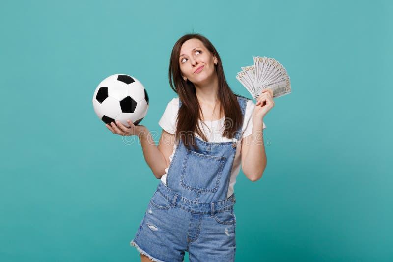 沉思与足球的年轻女人足球迷支持喜爱的队,金钱在美元钞票,现金金钱爱好者  免版税库存图片