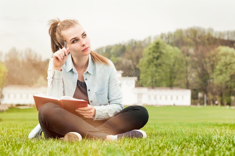 沉思严肃妇女坐外部和写在她的日志 库存图片