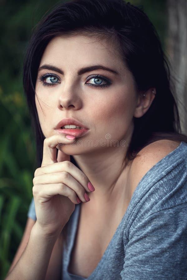 沉思体贴的性感的美丽的年轻白种人妇女特写镜头画象有黑发的,蓝眼睛,看在照相机 免版税库存图片