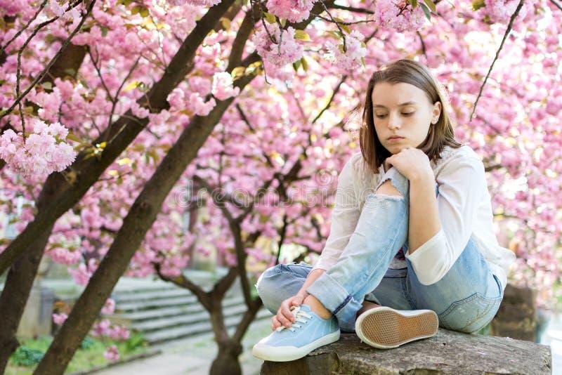 沉思和哀伤的青少年的女孩坐背景开花 免版税库存照片