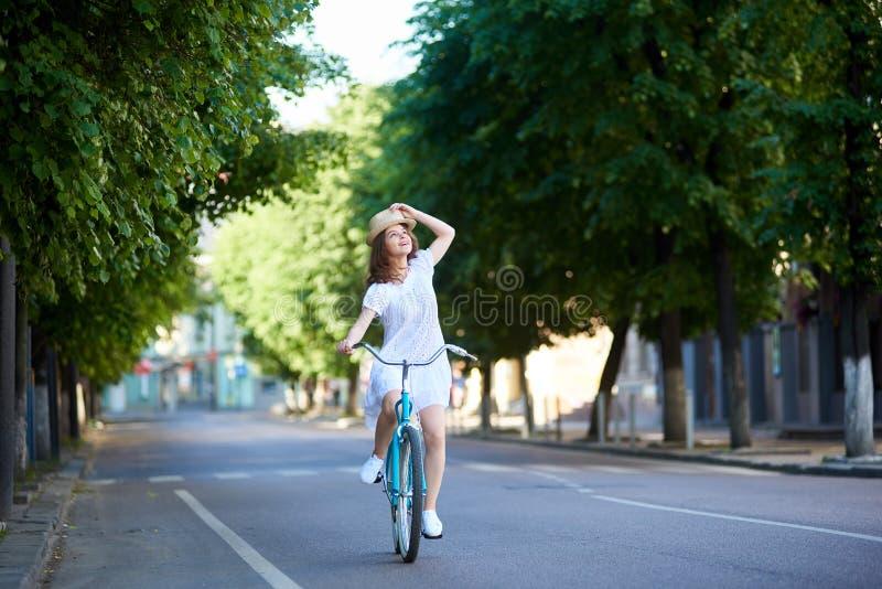沉思女孩在路乘坐在查寻减速火箭的自行车 免版税库存图片