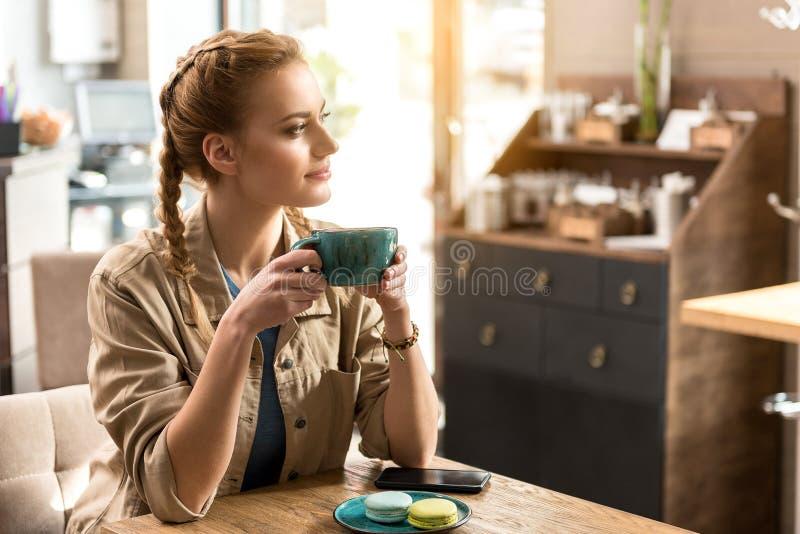 沉思女性品尝杯子饮料 免版税库存照片