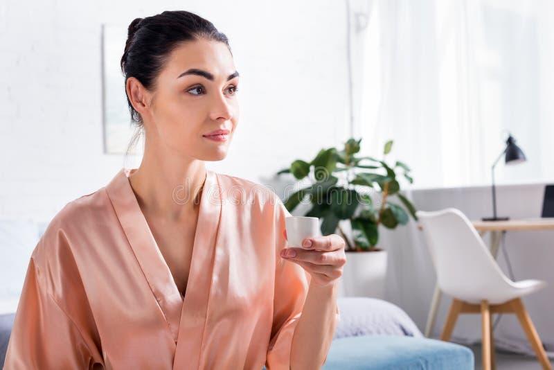 沉思妇女画象丝绸浴巾的有杯子的热的茶在手中在早晨 免版税库存照片