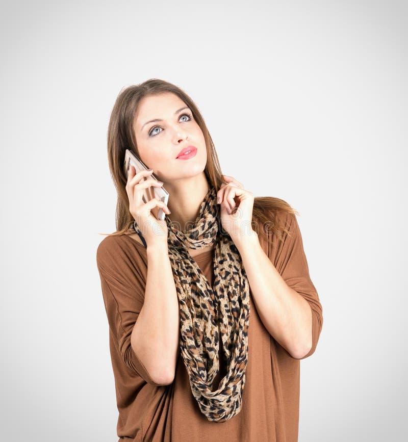 年轻沉思妇女谈话在手机 免版税库存图片