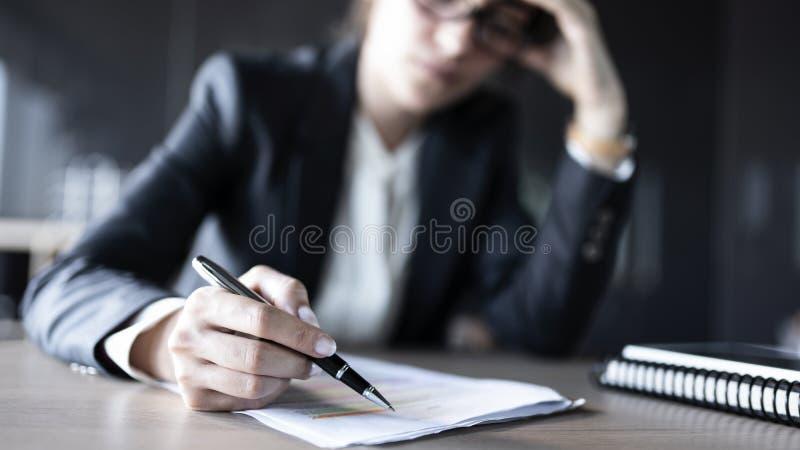沉思工作在办公室的女商人 免版税库存图片