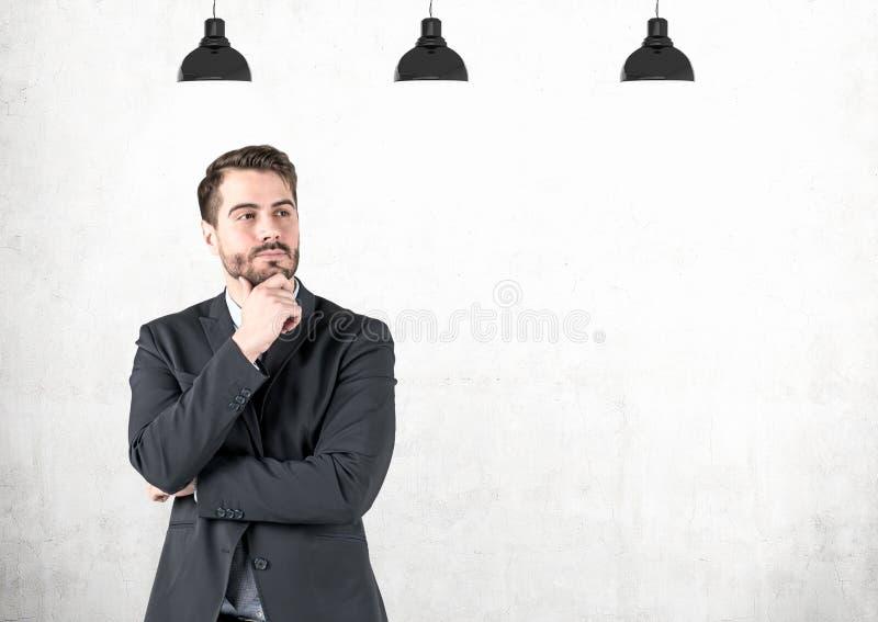 沉思年轻商人,混凝土墙 免版税图库摄影