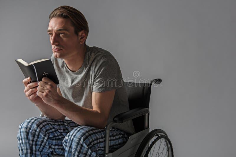 沉思残疾与在胳膊的圣经 库存照片