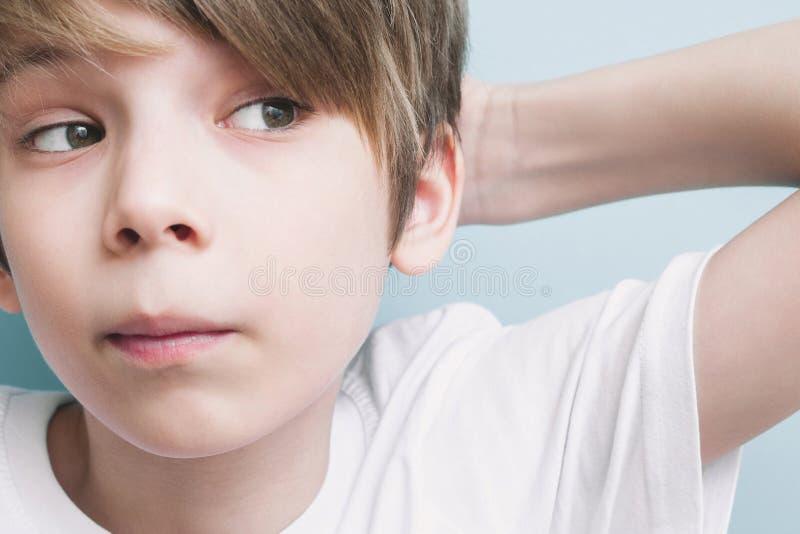 沉思男孩抓痕他的头 免版税库存图片