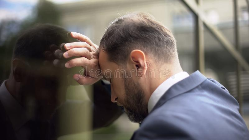 沉思男性倾斜在办公室墙壁,工作失败问题,失望 免版税库存照片