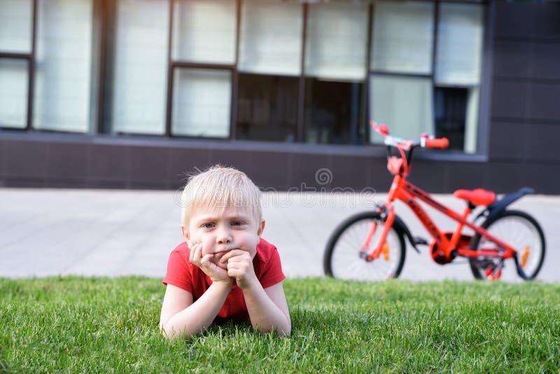沉思白肤金发的男孩基于草坪 自行车在背景中 库存照片