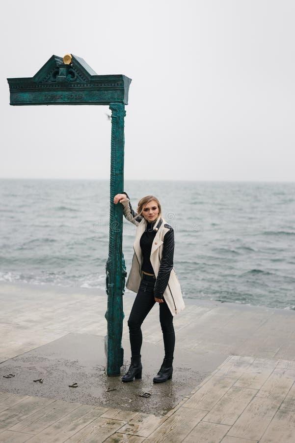 沉思美丽的女孩,由海等待某人路面的 免版税库存照片