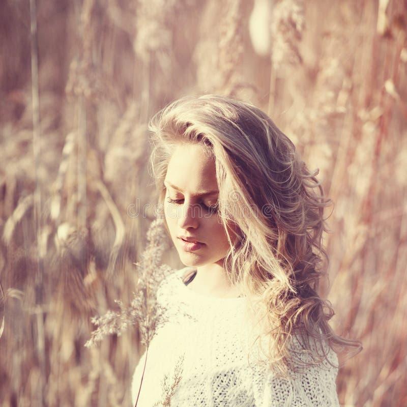 沉思美丽的白肤金发的女孩画象一个领域在白色套头衫,健康的概念和秀丽的 免版税库存图片