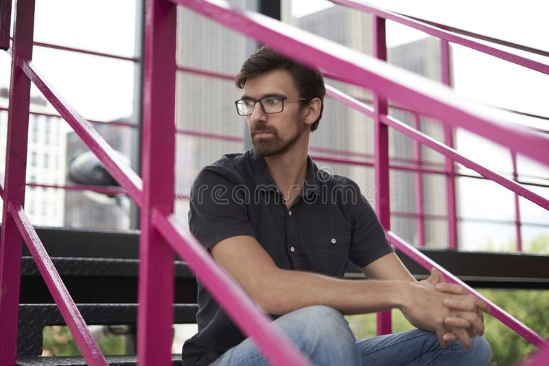 沉思英俊的人坐戴眼镜的台阶朝左边看 城市后边视图大厦 免版税图库摄影