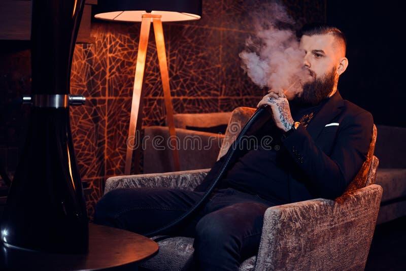 沉思被刺字的人坐扶手椅子并且开始抽烟水烟筒 免版税库存图片