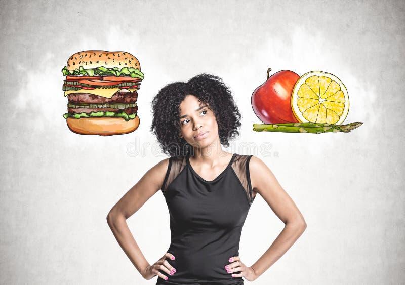 沉思非裔美国人的妇女,食物选择 库存照片