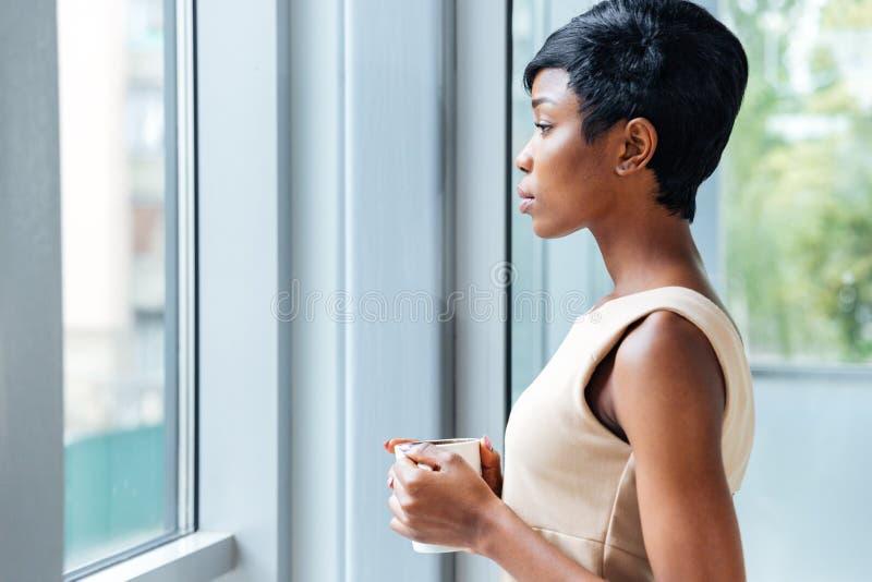 沉思非洲在窗口附近的女实业家饮用的咖啡在办公室 图库摄影