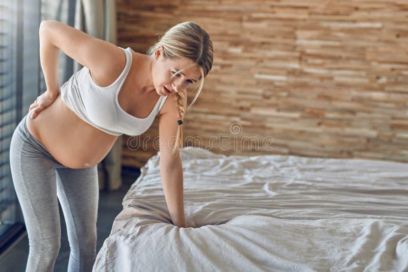 沉重遭受以后背疼痛的怀孕的年轻女人 免版税库存照片