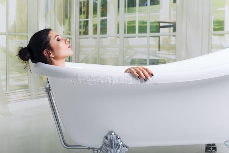 沐浴放松的妇女在浴微笑的放松与眼睛关闭了 免版税库存图片