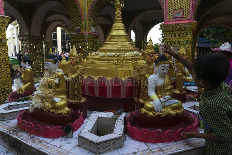 沐浴菩萨的男孩在缅甸寺庙-英尺长度塔在缅甸 免版税库存图片