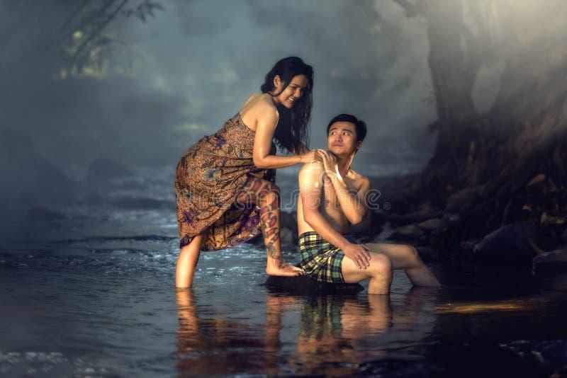 沐浴在小瀑布的亚洲夫妇 图库摄影