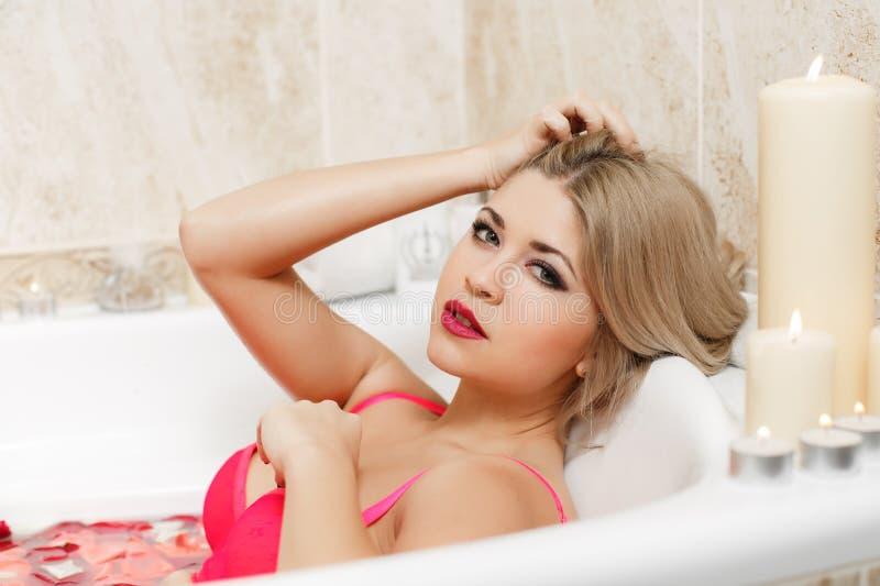 沐浴在浴缸的妇女用玫瑰花瓣填装了 库存图片