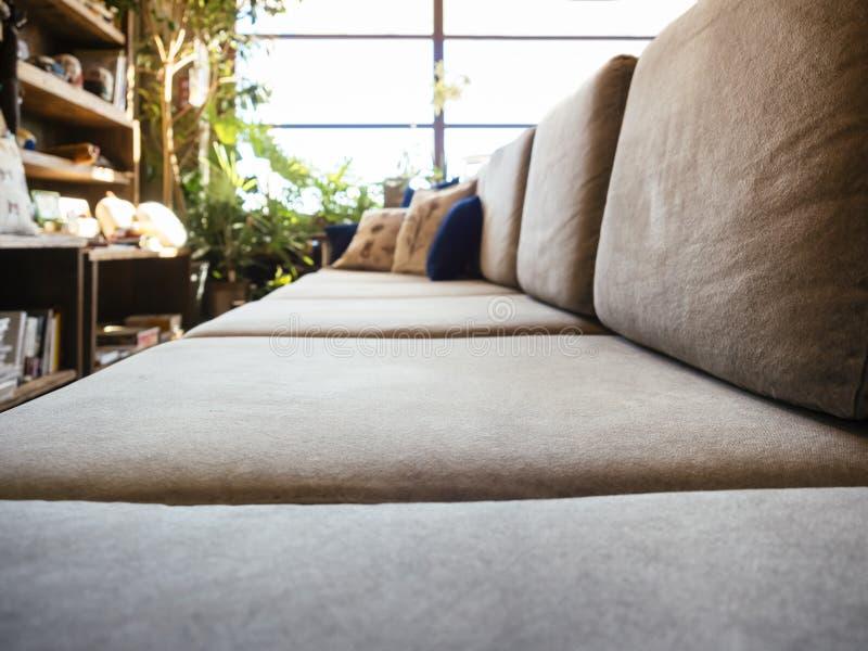 沙发位子在客厅与书架的阳光窗口里 库存图片