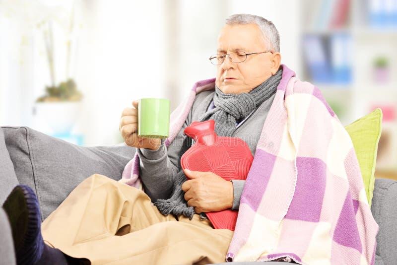 沙发的不适的人盖用毯子在家喝热的茶的 免版税库存照片