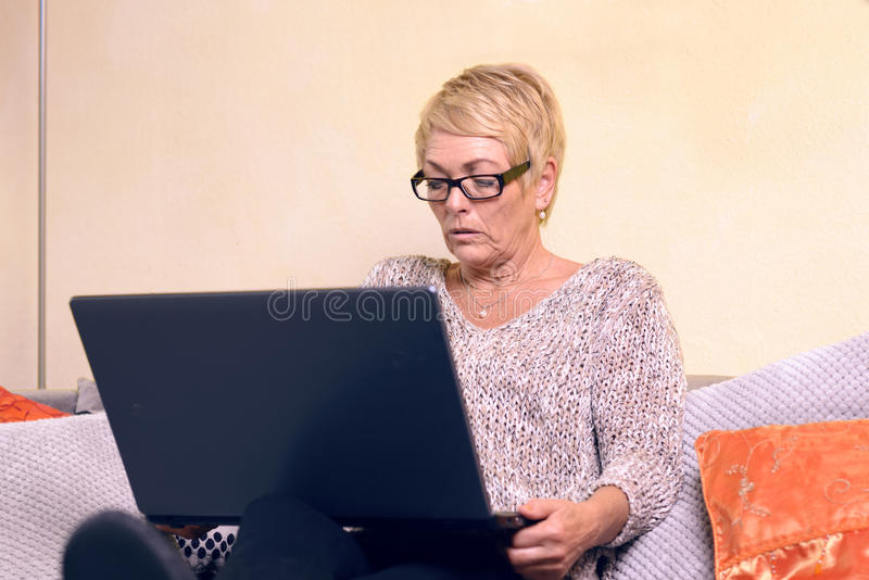 沙发的严肃的中古时期妇女有膝上型计算机的 库存图片