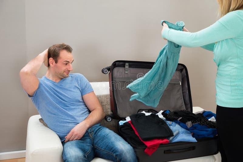 沙发的人,当妇女折叠的衣裳时 库存照片