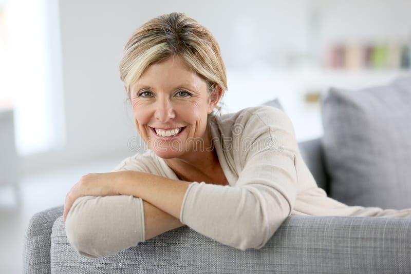 沙发的微笑的成熟妇女 库存图片