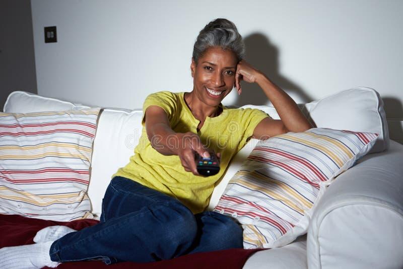 沙发的成熟非裔美国人的妇女看电视的 免版税图库摄影