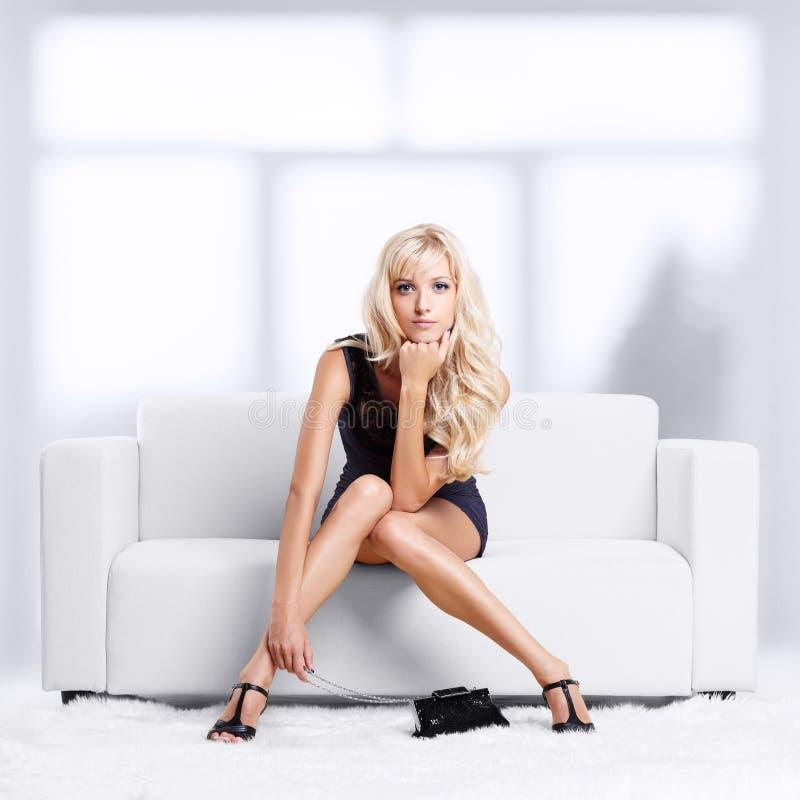 沙发的白肤金发的女孩 免版税图库摄影