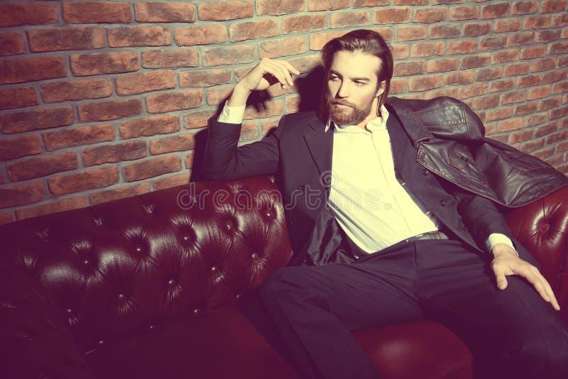 沙发的英俊的人 图库摄影