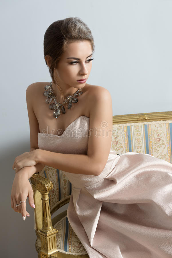 沙发的迷人的贵族女孩 库存图片