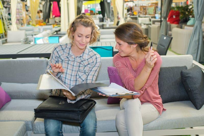 沙发读书小册子或杂志的两个妇女朋友 免版税图库摄影