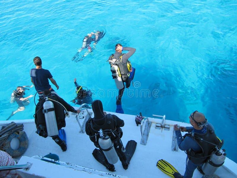 沙姆沙伊赫,埃及- 2009年12月29日:潜水者跳进从一条白色游艇的边的美丽的绿松石海洋在的 库存照片